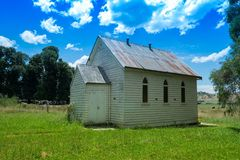 Historic church hall in the country side. Rura setting with green grass an blue skies with some clouds. This community church hall made of weatherboard and tin stock photos