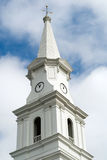 Historic Church Steeple. White historic church steeple with wind vane against  blue sky and clouds Stock Image