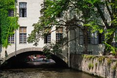 The historic city of Bruges with the river channels. The historic city of Bruges with the river channels and arches. Ivy winds along the white brick wall. The stock photography