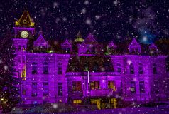 Historic city hall bathed in glow of Christmas Lights. Snow falling in the foreground of historic building royalty free stock photo