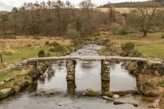 The historic Clapper Bridge made out of granite and crossing the East Dart River on Dartmoor National Park, England. A front on shot of the historic Clapper royalty free stock image