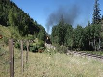 An historic coal fed passenger train wending its way through a mountain pass stock footage