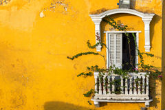Historic Colonial Balcony. Old colonial balcony in a historic yellow building in Cartagena, Colombia Royalty Free Stock Photo