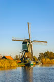 Historic Dutch windmill at the bank of a canal Royalty Free Stock Photo