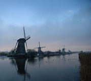 Historic dutch windmills in winter. Location is called Kinderdijk and everything is frozen Royalty Free Stock Images