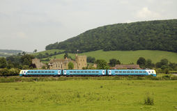 Historic English castle and a passenger train UK. Stokesay Castle and John the Baptist Church Shropshire England UK and a Arriva passenger train passing by Royalty Free Stock Photos