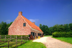 Historic farm house. Rural belgium, historical preserved farm house against vibrant blue sky.  Vintage, architecture, culture concept Royalty Free Stock Photography