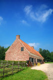 Historic farm house. Rural belgium, historical preserved farm house against vibrant blue sky.  Vintage, architecture, culture concept Royalty Free Stock Images