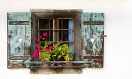 Historic farmhouse window with red geraniums. Royalty Free Stock Photo