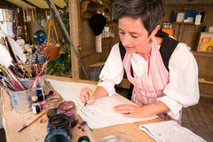 Historic female calligraphy writer. Friedberg, Germany - July 09, 2016: A female calligraphy writer is performing in the traditional way of the eighteenth stock images