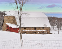 Historic Fieldstone Barn with fresh snow,USA. Pigeons huddle for warmth on the roof of this Century  old field-stone Barn in this cold January evening scene Royalty Free Stock Images