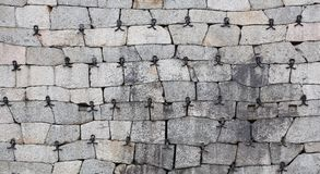 Historic fieldstone wall reinforced with wrought iron parts.  Royalty Free Stock Image