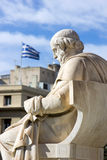 Historic greek statue with greek flag on the background Royalty Free Stock Photography
