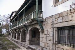 Historic  green wooden  balcony and stone wall. Green woden balcony in stone building hotel and stone wall Stock Photos