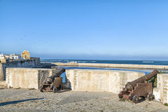 Historic guns standing in the old historic portuguese fortress city El Jadida in Morocco. At the coast of the shining blue Atlantic Ocean and a gorgeous old Royalty Free Stock Image