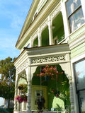 Historic house with balcony. Historic house in San Diego oldtown,  restored and freshly painted. Balcony with flowers hanging in front. Beautifully wooden carved Stock Image