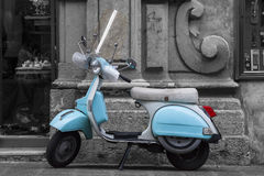 Historic Italian colored motorcycle scooter. Black and white. Historic Italian motorcycle scooter. An ancient Italian water colored motorcycle is parked in front Royalty Free Stock Photography