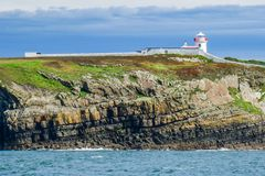 Historic Loop Head Peninsula Lighthouse stands above dramatic coastal cliff rock layers and ocean waves, County Clare, Ireland. stock photography
