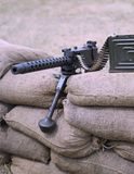 Historic machine gun with bullets over the sandbags in trench Royalty Free Stock Photo
