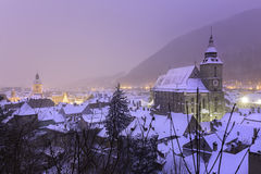 Historic medieval city of Brasov, Transylvania, Romania, in the winter. December 6th, 2015. The Black Church in the foreground and the square in the background Royalty Free Stock Photography