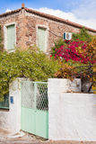 Historic mediterranean home with flower garden. Old greek stone house with lush blooming flower garden Royalty Free Stock Photography
