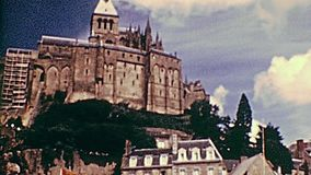 1970s Mont Saint-Michel. Historic Mont Saint-Michel panorama from car parking in the 70s. Saint Michael`s Mount Archival from 1976 in France. UNESCO World stock footage