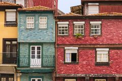 Colorful, old, weathered buildings with tiled and stucco facades in red, yellow, and blue hues in Porto, Portugal. Historic multi-story homes and buildings clad stock photos
