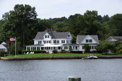 Historic New Enlgand mansion. S across the Thames river from wooden piers and wharfs, Old Mystic Seaport, Connecticut Stock Photo