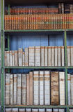Historic old books in library, wooden bookshelf Stock Photos