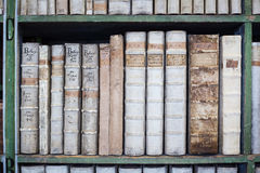 Historic old books in library, wooden bookshelf Stock Image