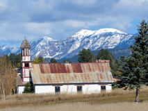 Abandoned church below snow covered mountains. Royalty Free Stock Photography