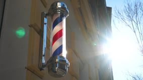 Historic old fashioned antique barber pole in a small town business barber shop. Barber shop vintage pole retro. Historic old fashioned antique barber pole in a stock video footage