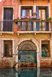 An historic orange apartment faces a watery canal in Venice Italy. An dilapidated and historic orange apartment with flower boxes  and cracking paint faces a Royalty Free Stock Image