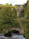 Historic packhorse bridge in Hebden Bridge crossing the river. With trees and surrounding houses Stock Photos