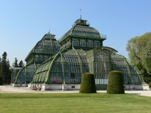 Historic palm house. In vienna´s castle park with sprinklers on the lawn in front royalty free stock photo