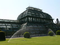 Historic palm house. In vienna´s castle park with sprinklers on the lawn in front stock photo