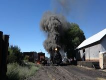 An historic passenger train at the station in new mexico. A preserved steam locomotive blowing black smoke as it departs for an excursion through the rockies stock video footage