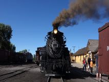 An historic passenger train at the station in new mexico. A preserved steam locomotive blowing black smoke as passengers board for an excursion stock video