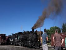 An historic passenger train at the station in new mexico. A preserved steam locomotive blowing black smoke as passengers board for an excursion stock footage