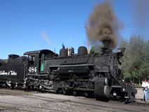 An historic passenger train at the station in new mexico. A preserved steam locomotive blowing black smoke as passengers board for an excursion stock video footage