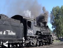 An historic passenger train at the station in new mexico. A preserved steam locomotive blowing black smoke while passengers board for an excursion stock video