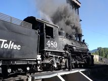 An historic passenger train at the station in new mexico. A preserved steam locomotive blowing black smoke while passengers board for an excursion stock footage