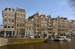 Historic residential buildings with commercial shops on the ground floor on the corner of Prinsengracht canal and Reestraat bridge Stock Images
