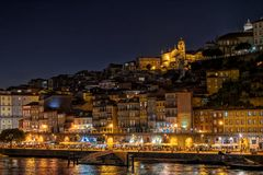 The thriving Ribeira Waterfront at dusk, Porto, Portugal. The historic Ribeira waterfront - Cais de Ribeira and the famous apartment blocks at dusk. The royalty free stock photo
