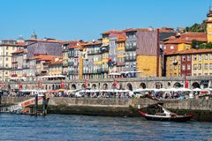 The bustling Ribeira Waterfront, Porto, Portugal. The historic Ribeira waterfront - Cais de Ribeira and the famous apartment blocks. The waterfront has many royalty free stock image
