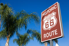 Historic route 66 highway sign with palm tree and a blue sky. An historic route 66 highway sign with palm tree branches and a blue sky background Stock Photography