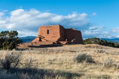 Ruins of an old adobe Spanish mission church in a grassy meadow in Pecos National Historical Park stock photo