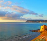 Historic Saracen tower on beach in Mediterranean city of Alassio on Sunset,a popular resort town on provincia Savona,Liguria,Italy stock image