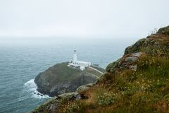 South Stacks Lighthouse. The historic South Stack Lighthouse is located on a small island reached via a descent of 400 steps down the steep mainland cliffs Stock Image