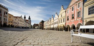 Historic Square,Czech Republic. Historic square, Telc City, Czech Republic - bench on stone paved square, unique buildings, blue sky Royalty Free Stock Images